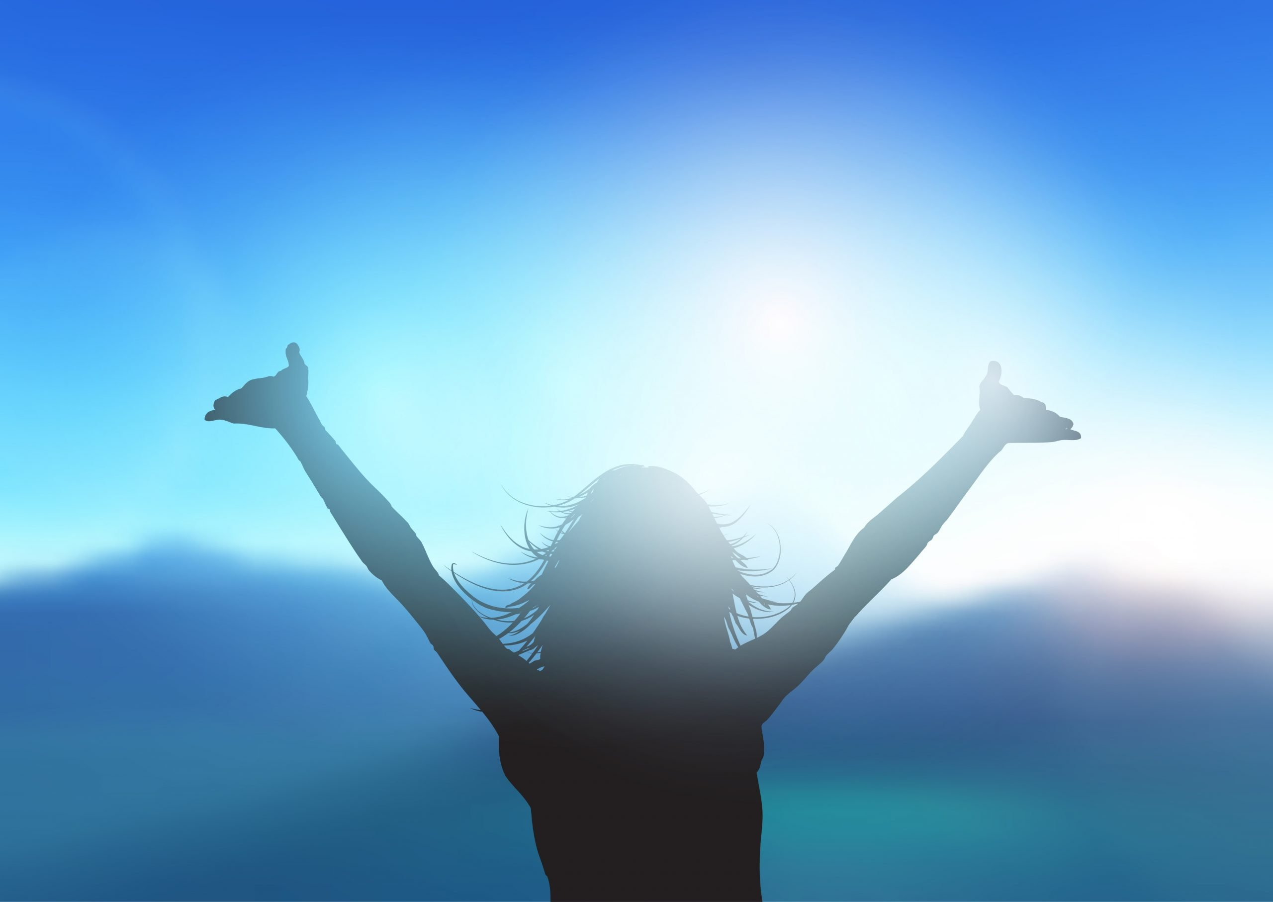 Silhouette of a female with arms raised against mountain landscape